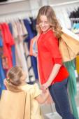 Happy mother with her daughter and lots of new purchases in pack — Stock Photo
