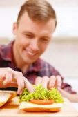 Close up of man decorating bread with lettuce — Stock Photo