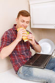 Man eating sandwich and holding notebook — Stock Photo