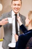 Woman fixing tie of handsome man — Stock Photo