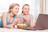Two young girls eating popcorn — Stock Photo
