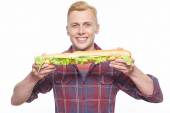 Smiling man standing with long loaf sandwich — Stock Photo