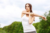 Young sportive girl stretching her arms — Stock Photo