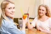 Two women clinking glasses with cocktails in cafe — Stock Photo