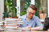 Young student working in a library — Stock Photo