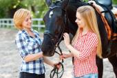 Happy sisters  standing with the horse  — Stock Photo
