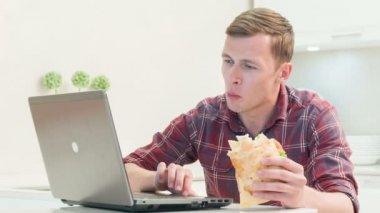 Usměvavý člověk jíst sendvič před počítač — Stock video