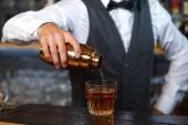 Bartender mixing drinks — Stock Photo