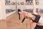 Vänner göra stretchingövningar i gym — Stockfoto