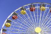 Colorful ferris wheel and blue sky at amusement park — Stock Photo