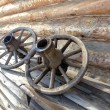 Old wooden wheel on the background of village house wall — Stock Photo #66394857