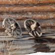 Old wooden wheel on the background of village house wall — Stock Photo #66394871