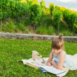 Portrait of adorable little girl resting outdoors and reading a book on a nice summer evening — Stock Photo #59231093