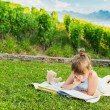 Portrait of adorable little girl resting outdoors and reading a book on a nice summer evening — Stock Photo #59231103