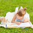 Portrait of adorable little girl resting outdoors and reading a book on a nice summer evening — Stock Photo #59231323