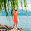 Summer portrait of a cute little girl wearing orange dress, standing next to lake on a nice sunny day, outdoors — Stock Photo #59231441