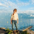 Sunset portrait of a cute little girl next to beautiful lake, wearing beige knitted pullover and jeans — Stock Photo #59235421