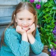 Outdoor portrait of a cute little girl sitting on steps in a city on a nice spring day — Stock Photo #59237597