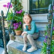 Outdoor portrait of a cute little girl sitting on steps in a city on a nice spring day — Stock Photo #59237621
