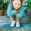 Outdoor portrait of a cute little girl sitting on steps in a city on a nice spring day — Stock Photo #59237629