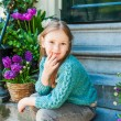 Outdoor portrait of a cute little girl sitting on steps in a city on a nice spring day — Stock Photo #59237659