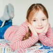 Beautiful little girl resting on a bed — Stock Photo #59238289