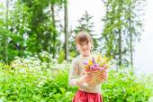 Portrait of a cute little girl with basket with flowers — Stock Photo