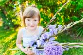 Outdoor portrait of a cute little girl with beautiful bouquet of purple flowers — Stock Photo