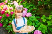 Outdoor portrait of a cute little girl with apple pie going to neighborhood party — Stock Photo