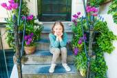 Outdoor portrait of a cute little girl sitting on steps in a city on a nice spring day — Zdjęcie stockowe