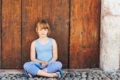 Outdoor portrait of a cute little girl sitting on a ground in an old city — Stock Photo