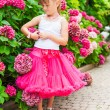 Beautiful little girl wearing bright pink tutu skirt and white top, standing next to bushes of hydrangea, vertical portrait — Stock Photo #59273445