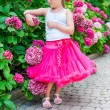 Beautiful little girl wearing bright pink tutu skirt and white top, standing next to bushes of hydrangea, vertical portrait — Stock Photo #59273481
