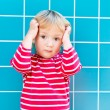 Outdoor portrait of a cute toddler boy wearing red top with white stripes, holding his head, blue tiles on background — Stock Photo #59296013