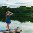 Outdoor portrait of a cute little girl, standing on a pier and looking on a beautiful lagoon in the evening — Stock Photo #59297153