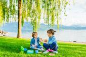 Adorable children having a picnic next to beautiful lake on a nice summer evening — Stock fotografie