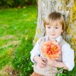 Outdoor portrait of a cute toddler boy on a nice sunny day, sitting under the tree, holding beautiful peony flower — Stock Photo #59309945