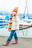 Outdoor portrait of a cute little girl wearing jacket and colorful hat and scarf — Fotografia Stock