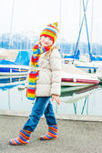 Outdoor portrait of a cute little girl wearing jacket and colorful hat and scarf — Foto de Stock