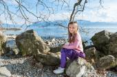 Cute little girl resting next to lake on a nice spring day — Zdjęcie stockowe
