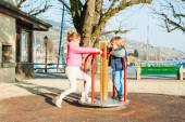 Adorable children having fun on a playground on a nice sunny spring day, playing with mary-go-ground — Zdjęcie stockowe