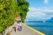 Outdoor portrait of a cute little girl on a bicycle next to beautiful lake on a nice sunny day — Zdjęcie stockowe