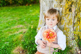 Outdoor portrait of a cute toddler boy on a nice sunny day, sitting under the tree, holding beautiful peony flower — Zdjęcie stockowe