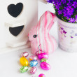Colorful easter decoration with chocolate eggs, bunny, purple bell flowers and white bird house — Stock Photo #59326117