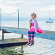 Outdoor portrait of a cute little girl sitting on a pier — Stock Photo #59326273