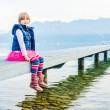 Outdoor portrait of a cute little girl sitting on a pier — Stock Photo #59326345