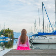 Cute little girl watching boats on the lake, sitting on a pier, view from the back — Stock Photo #59326449