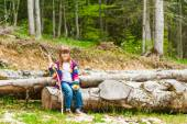Outdoor portrait of a cute little girl, sitting on a fallen tree in a forest on a nice sunny day — Zdjęcie stockowe