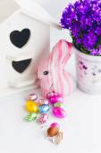 Colorful easter decoration with chocolate eggs, bunny, purple bell flowers and white bird house — Stock Photo