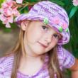 Close up portrait of a cute little girl in a beautiful knitted violet hat with flowers — Stock Photo #59363221